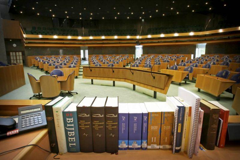 DEN HAAG - Een lege vergaderzaal met op de voorgrond de attributen van de voorzitter en de griffie, wetboeken, woordenboeken, de koran, twee bijbelvertalingen en.... een alarmnummer op de telefoon